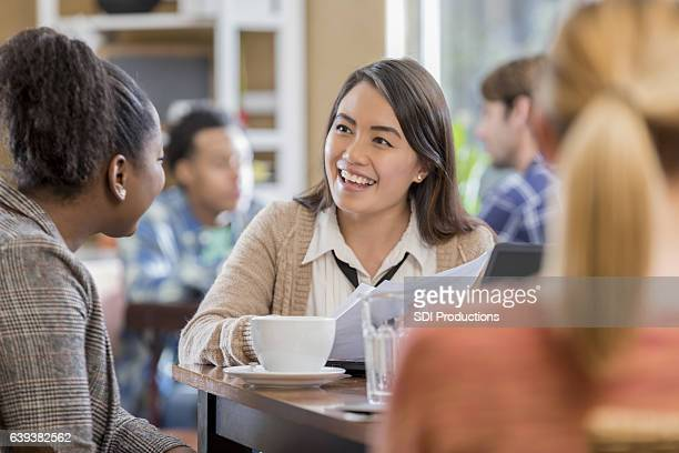 Cheerful young Asian woman meets with colleague