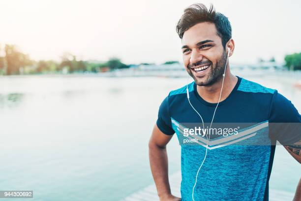 cheerful young athlete outdoors by the river - homens imagens e fotografias de stock