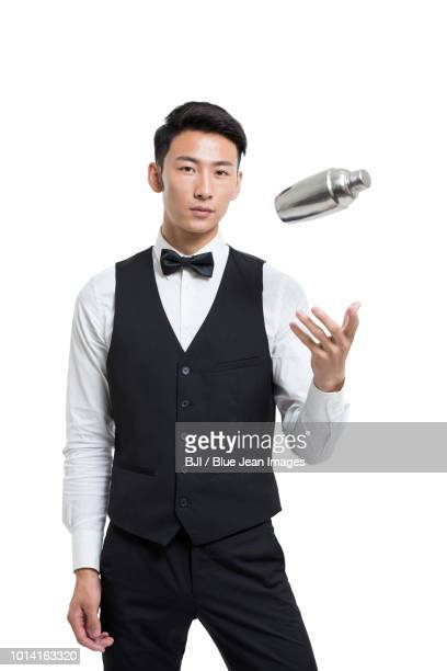 cheerful young bartender shaking drinks - waistcoat stock pictures, royalty-free photos & images