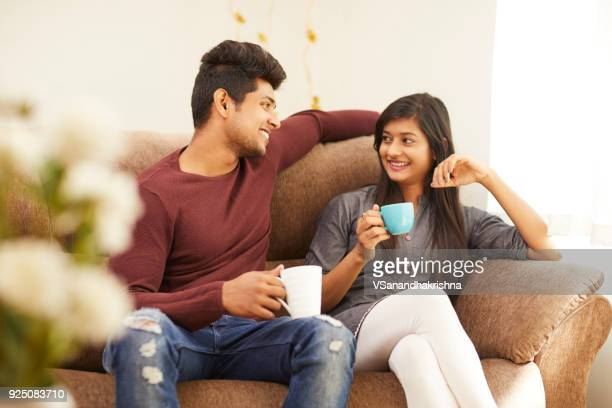 cheerful young beautiful couple having coffee together on sofa - indian culture stock pictures, royalty-free photos & images
