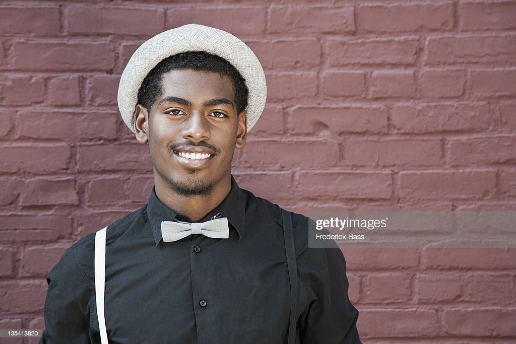 A cheerful young black man wearing bow tie, suspenders and hat : Stock Photo