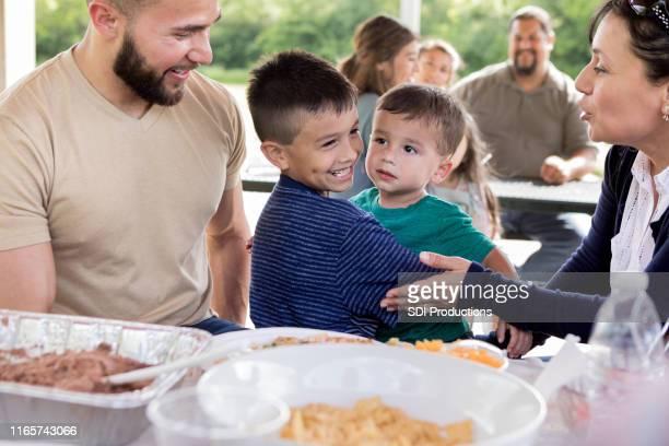 家族の再会で陽気な若い兄弟 - ポットラック ストックフォトと画像