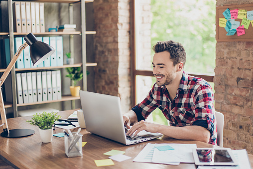 Cheerful young brunet freelancer is smiling, typing on his laptop in nice modern work station at home, in casual smart wear 932763106