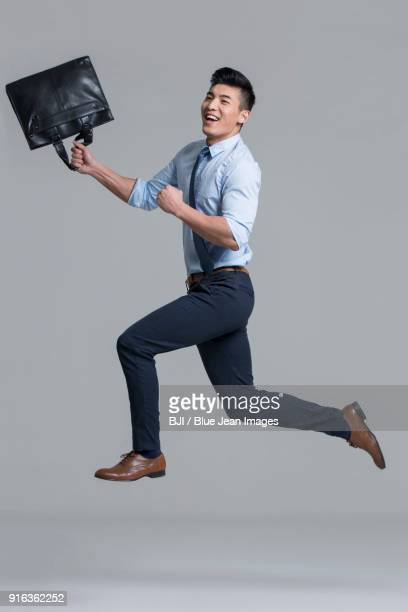 cheerful young businessman punching the air - legs apart stock pictures, royalty-free photos & images