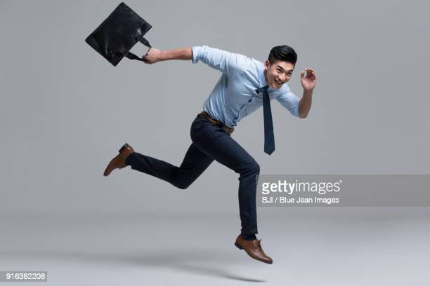 cheerful young businessman running with briefcase - shirt and tie stock pictures, royalty-free photos & images