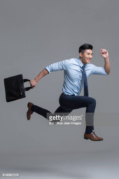 cheerful young businessman running with briefcase - legs apart stock pictures, royalty-free photos & images