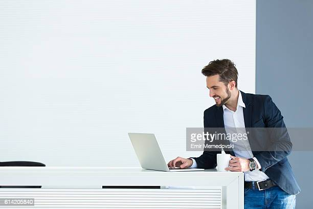 Cheerful young businessman using laptop while having coffee break.