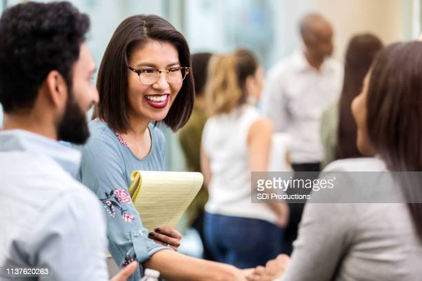 cheerful young businesswoman greets new client - greeting stock pictures, royalty-free photos & images
