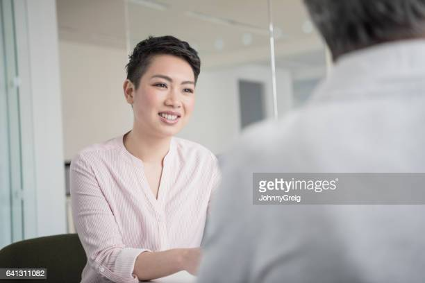 Cheerful young businesswoman in office with short dark hair