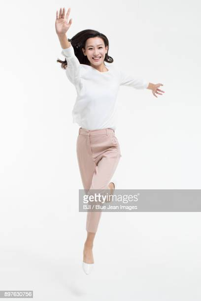 Cheerful young businesswoman jumping