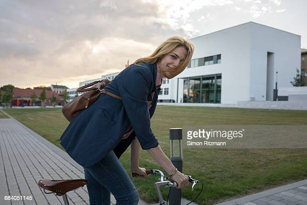 Cheerful young businesswoman riding bicycle