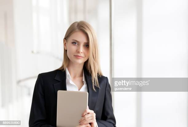 Cheerful young businesswoman standing with digital tablet