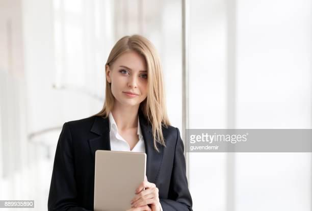 Femme d'affaires jeune gai debout avec tablette numérique
