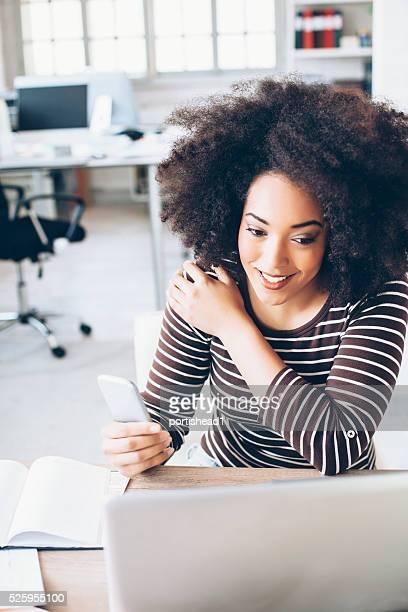 Joyeuse jeune femme d'affaires utilisation du téléphone au travail