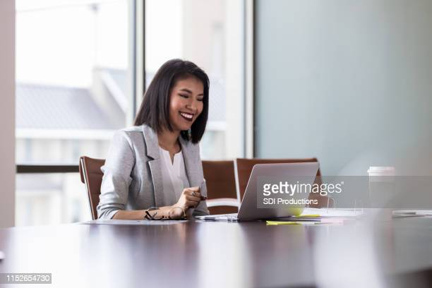 cheerful young businesswoman video chats with colleague - videoconferenza foto e immagini stock