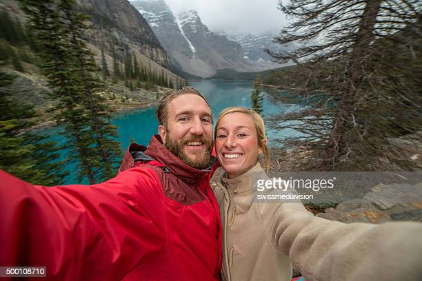 Cheerful young couple at Moraine lake taking a selfie portrait