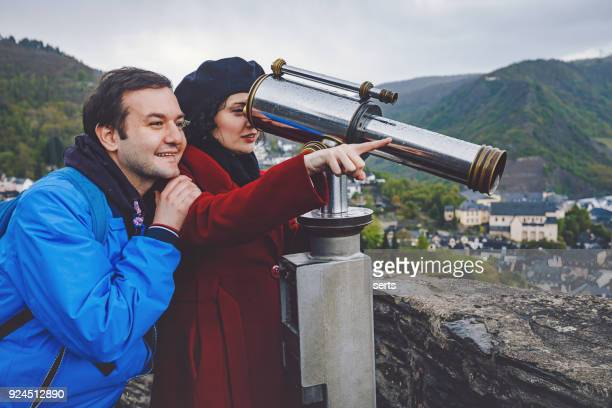 Cheerful young couple enjoying sightseeing telescope against Cochem town in Germany