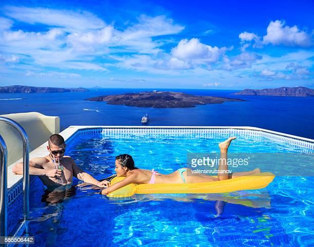 Cheerful young couple having fun at swimming pool