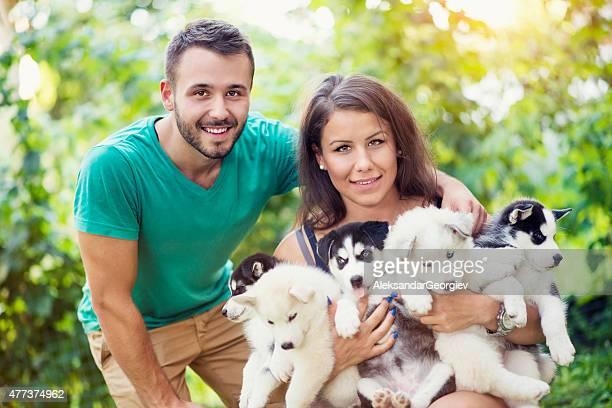 Fröhlich junges Paar Holding fünf wunderschönen Husky Baby-Klößchen