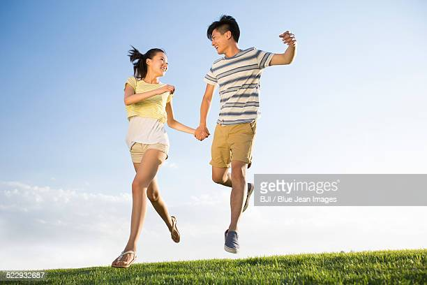 Cheerful young couple holding hands jumping on grass