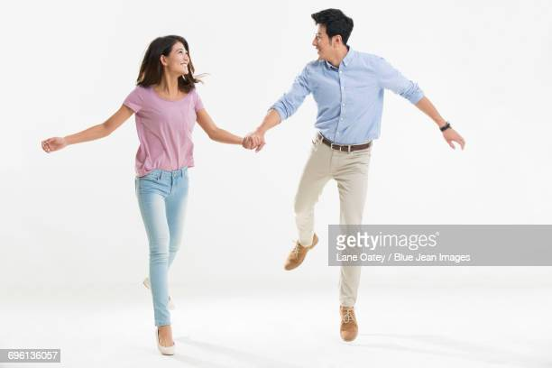 Cheerful young couple holding hands