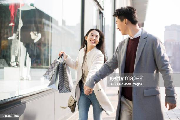 cheerful young couple holding hands walking with shopping bags - three quarter front view stock pictures, royalty-free photos & images