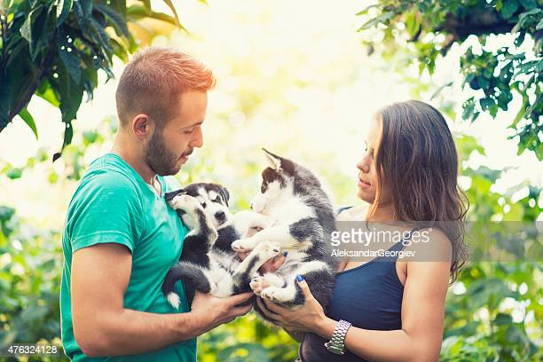 Fröhlich Junges Paar Holding zwei schöne Husky Baby-Klößchen