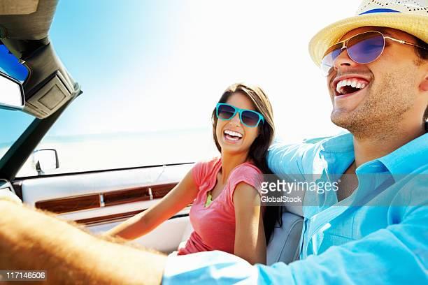 Cheerful young couple in a convertible car going for vacation