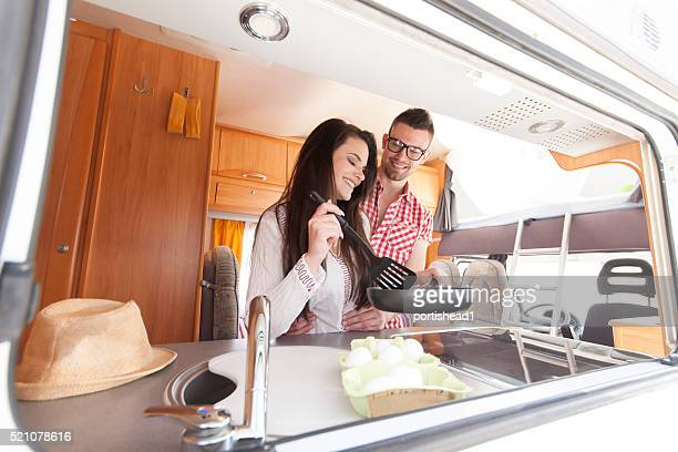 Cheerful young couple making breakfast inside of a camper van