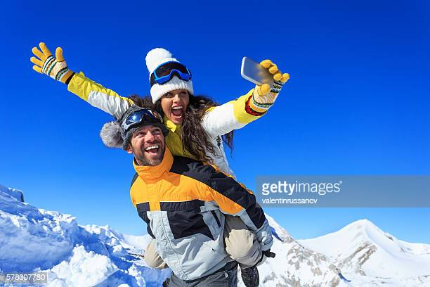 Cheerful young couple making winter selfie