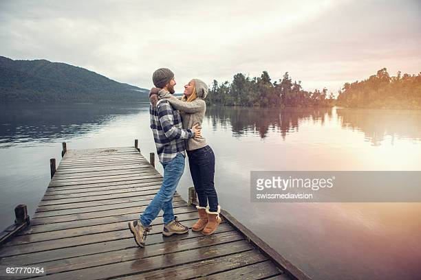 Cheerful young couple on a lake pier being affectionate
