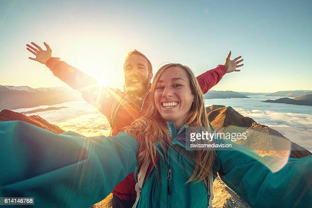 cheerful young couple on mountain top take selfie - mountain peak stock pictures, royalty-free photos & images