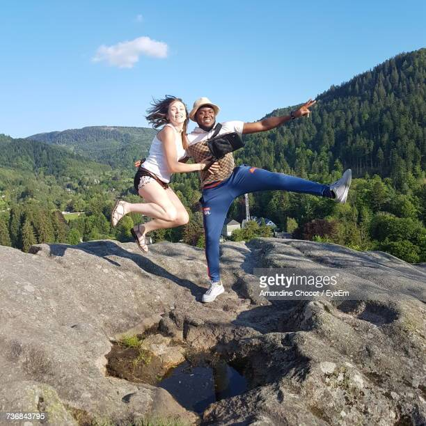 Cheerful Young Couple On Rock Formation Against Mountain