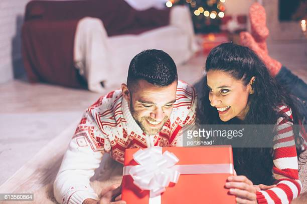 Cheerful young couple opening christmas present