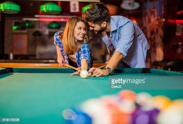 Cheerful young couple playing pool in the pub.