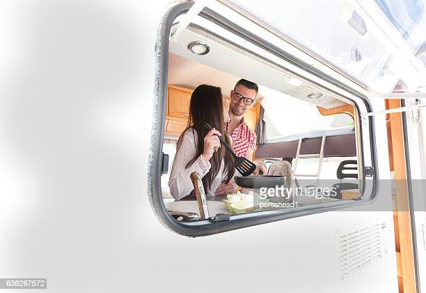 Cheerful young couple preparing breakfast inside of a camper