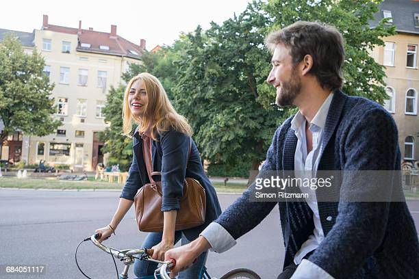 Cheerful young couple riding bicycles in the city