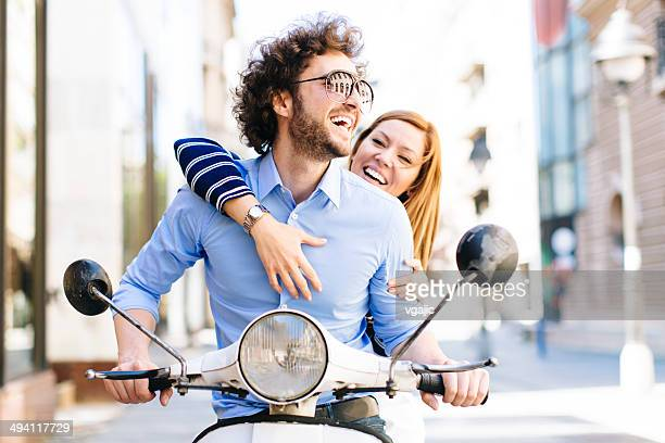 Cheerful Young Couple Riding on a motorbike.