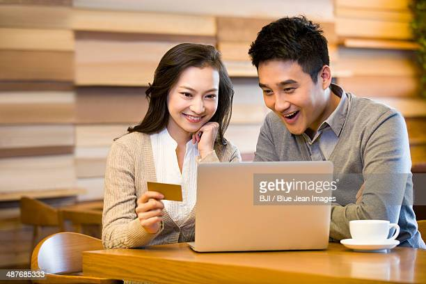 Cheerful young couple shopping online in cafe