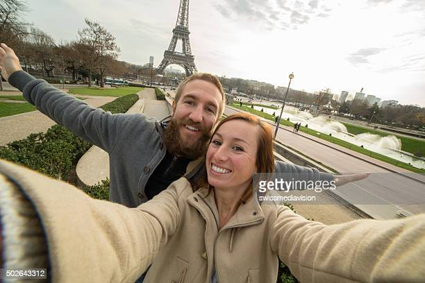 Cheerful young couple takes selfie portrait at Eiffel tower, Paris