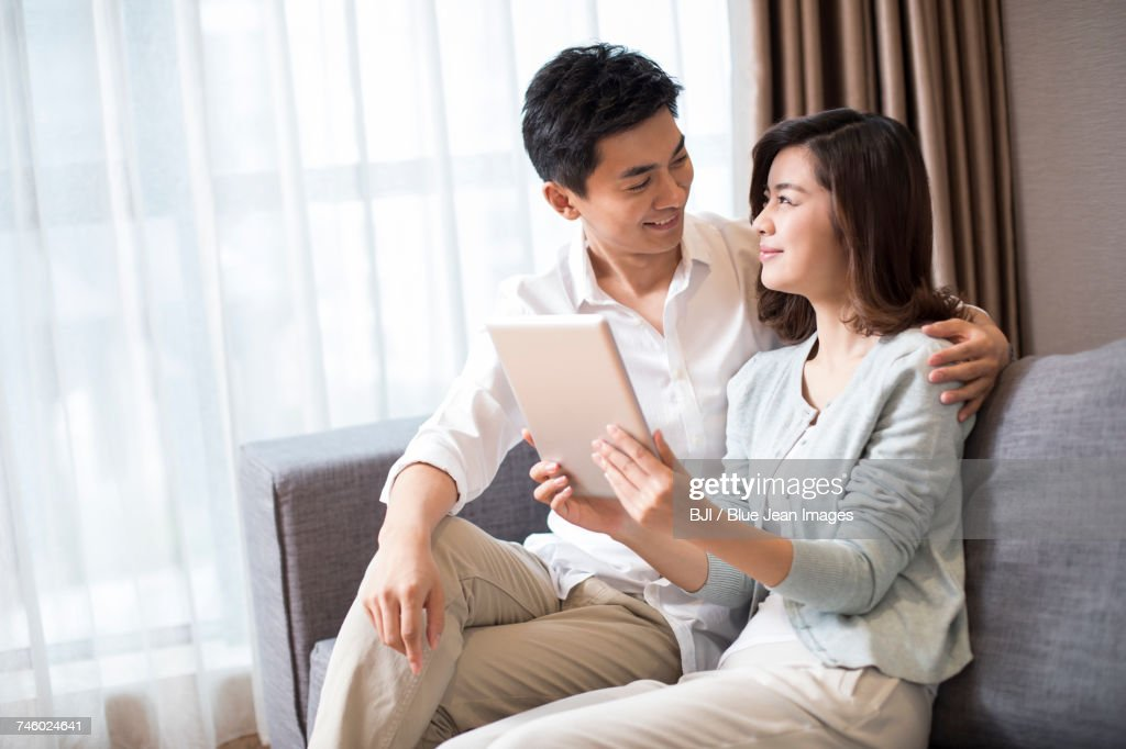 Cheerful young couple using digital tablet at home : 圖庫照片