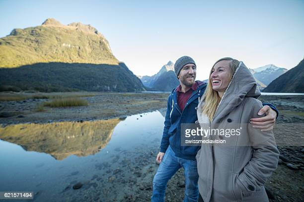 Cheerful young couple walking by the lake shore