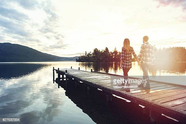 Cheerful young couple walking hand to hand on wooden pier