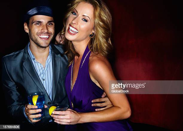 Cheerful young couple with their drinks in nightclub