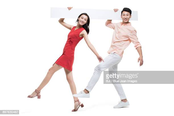 Cheerful young couple with whiteboard