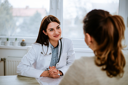 Cheerful young doctor listening to a patient in the office. 914952832