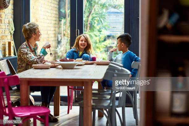cheerful young family eating lunch together - adoption stock pictures, royalty-free photos & images