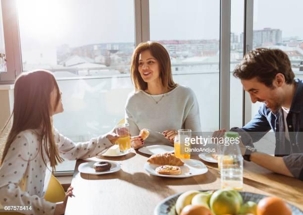 bonne humeur jeune famille prenant son petit déjeuner ensemble