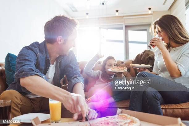 cheerful young family having pizza for lunch