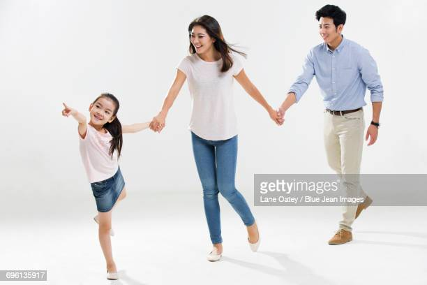 Cheerful young family holding hands running